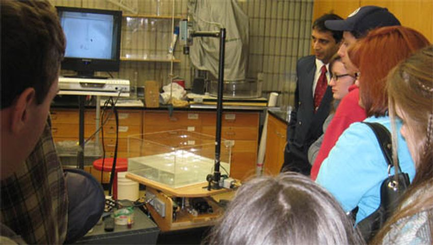 Students watching one of Amit Tandon's demonstrations using the rotating fluids table.